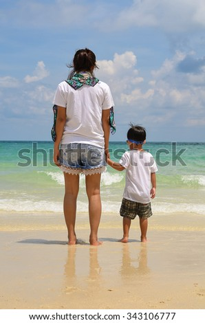 Woman and boy holding hands and standing on the beach