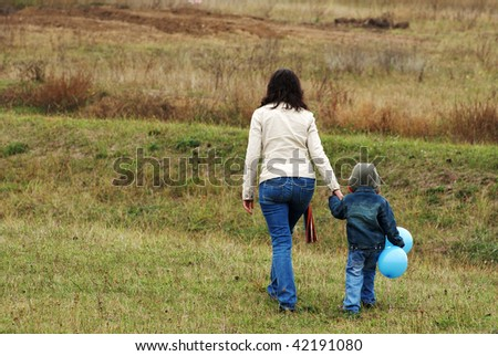 Woman and boy with blue balloon on the meadow escape - stock photo