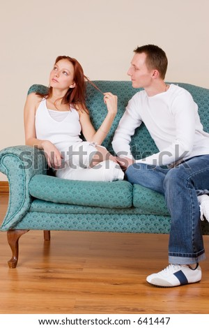 Woman and boyfriend sitting on couch, talking