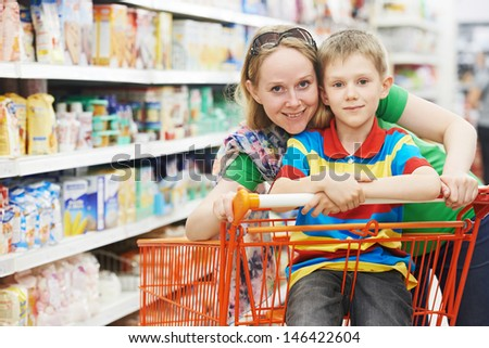 woman and child boy during family shopping with trolley at supermarket - stock photo