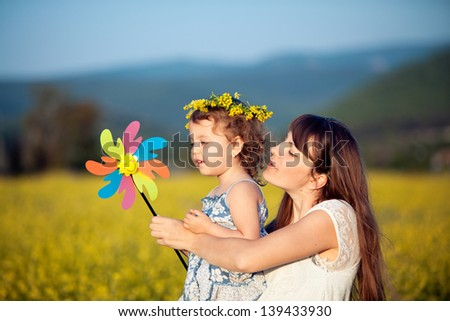 Woman and child playingwith toy wind turbine in summer field - stock photo
