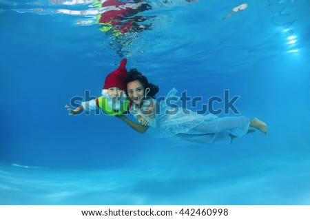 Woman and child presenting underwater fashion in pool - stock photo