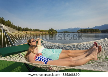 Woman and child relaxing in a hammock on a beautiful Mountain Lake - stock photo