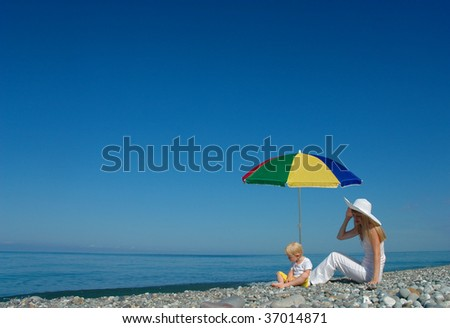 Woman and child sit under an umbrella on the beach