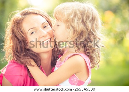 Woman and child with bouquet of flowers against green blurred background. Spring family holiday concept. Women's day - stock photo