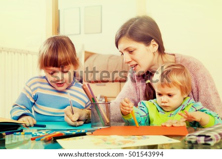 Woman and  children together drawing with pencils in home interior