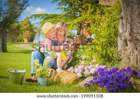 Woman and daughter doing garden work in summer sunny day - stock photo