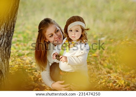 woman and daughter in fall time - stock photo