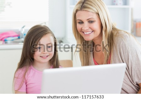 Woman and daughter looking at the monitor smiling in kitchen