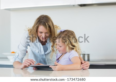 Woman and daughter using tablet computer together at table in kitchen - stock photo