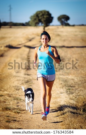 Woman and dog running in country side dirt track. Female runner exercising and training with her pet for cross race. Fitness girl on summer rural landscape. - stock photo