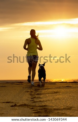Woman and dog running toward the sun on summer beach in a beautiful golden sunset. Sport girl and her pet training together. - stock photo