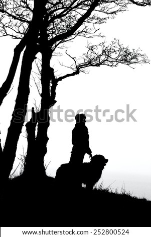 woman and dog silhouettes under trees, monochrome - stock photo