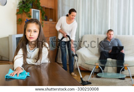 Woman and girl doing general cleaning, man having rest - stock photo