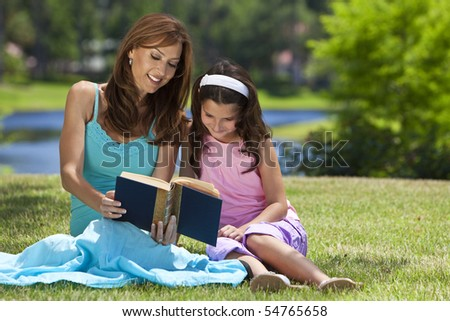 Woman and girl, mother and daughter, reading a book together outside in the countryside - stock photo