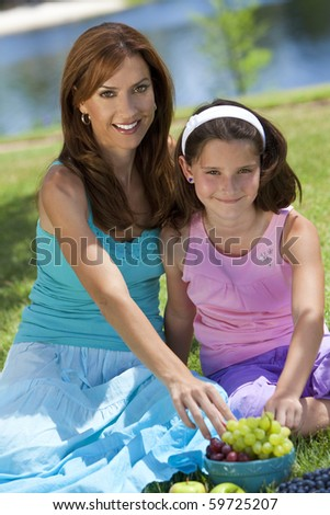 Woman and girl, mother and daughter, together outside in the countryside eating healthy fruit at a picnic by a lake - stock photo