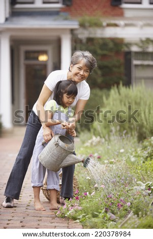 Woman and girl watering flowers - stock photo