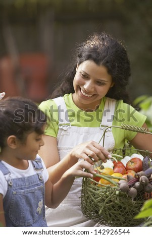 Woman and girl with basket of vegetables - stock photo