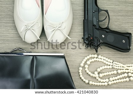 Woman and gun, Pistol and woman accessories, Handgun and accessories, Stylish set for girls. Women accessories, Still life of fashion woman. purse, necklace, women shoes. (Color Process) - stock photo