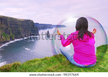 Woman and her aura at meditation on Irish cliffs