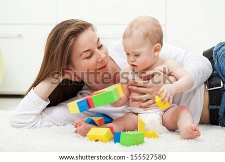 Woman and her baby boy playing with colorful blocks