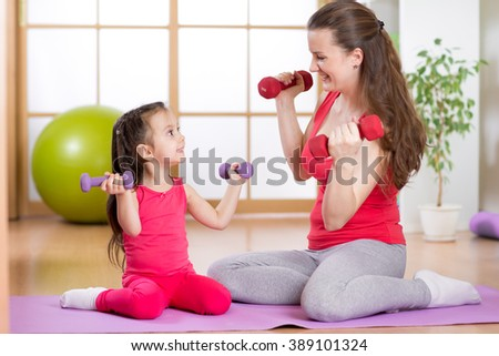 Woman and her child daughter doing fitness exercises  with dumbbells - stock photo