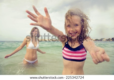 Woman and her daughter having fun in the sea. - stock photo