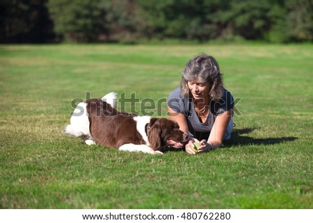 woman and her dog playing in the field