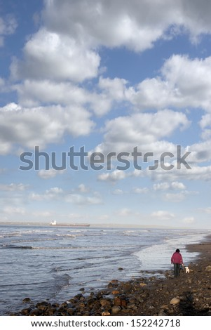 woman and her dog taking a walk along Beale beach in county Kerry Ireland