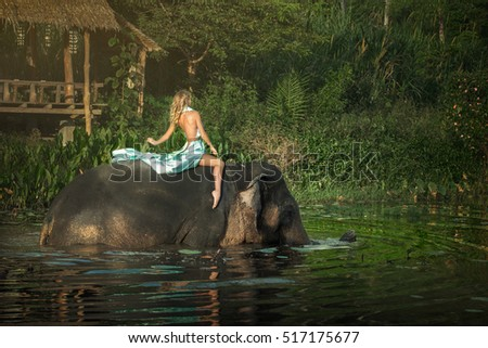 Woman and her elephant at the lake