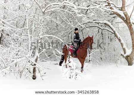 Woman and her horse cantering in fresh snow  - stock photo