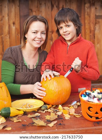Woman and her son preparing for Halloween - carving a pumpkin jack-o-lantern - stock photo