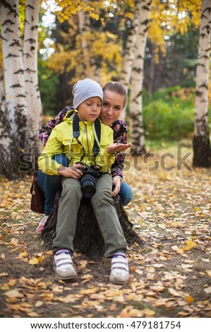 Woman and her son with camera in autumn forest