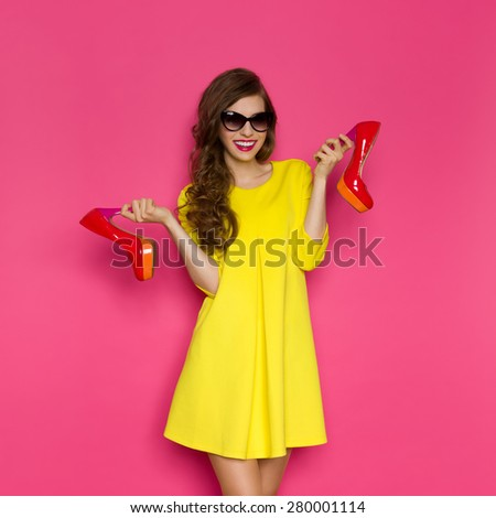 Woman And High Heels. Smiling young woman in yellow mini dress and sunglasses holding two red high heels. Three quarter length studio on pink background. - stock photo