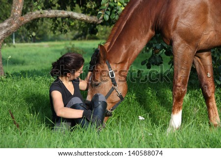 Woman and horse resting at the grazing in summer