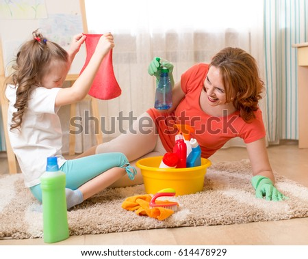 Lovely Woman And Kid Girl Playing Before Housework. Mother And Child Daughter Ready  To Room Cleaning
