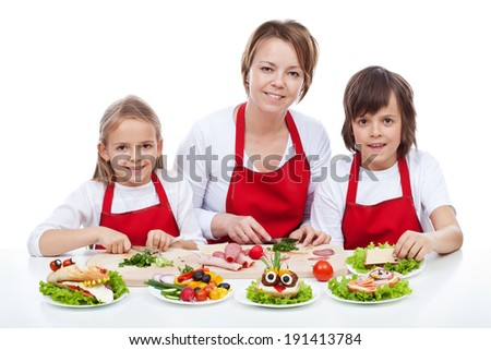 Woman and kids making creative food creature sandwiches together - isolated - stock photo