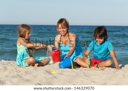 Woman and kids on the beach - playing with sand - stock photo