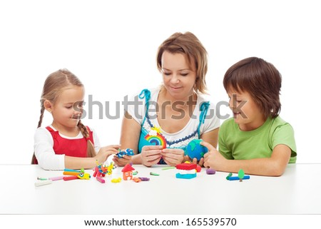 Woman and kids playing with colorful clay molding different shapes - stock photo