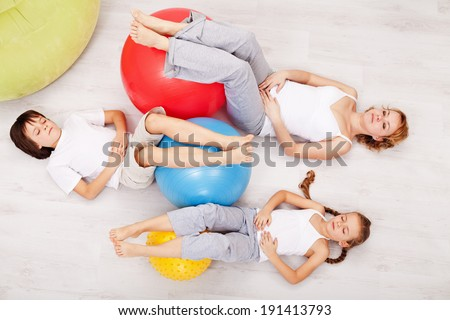 Woman and kids relaxing after gymnastic exercise - laying on the floor with closed eyes