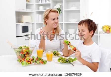 Woman and little boy having a healthy salad for snack