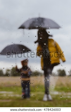 Woman and little boy outdoors under umbrella silhouette through wet window