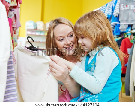 woman and little girl choosing and trying on clothes during shopping at garment supermarket - stock photo