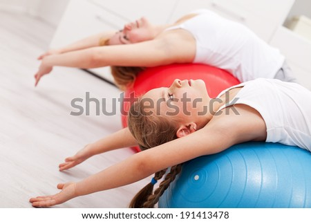 Woman and little girl exercising - stretching on large gymnastic balls, closeup