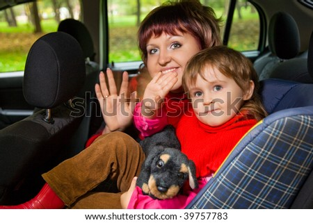 woman and  little girl  Greeting to wave hands in car in park - stock photo