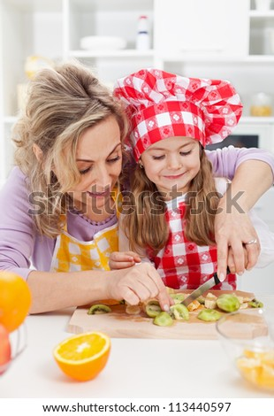 Woman and little girl making fresh fruits snack together - healthy eating concept