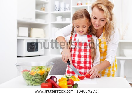 Woman and little girl preparing a vegetables salad in the kitchen