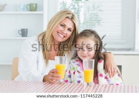 Woman and little girl sitting at the kitchen having a glass of juice at breakfast - stock photo