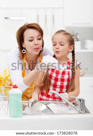 Woman and little girl washing dishes in the kitchen - having fun with the foam - stock photo