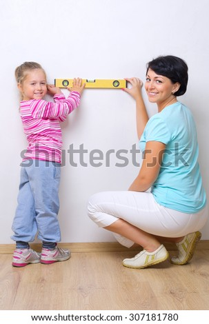 Woman and little girl with measurement level - stock photo
